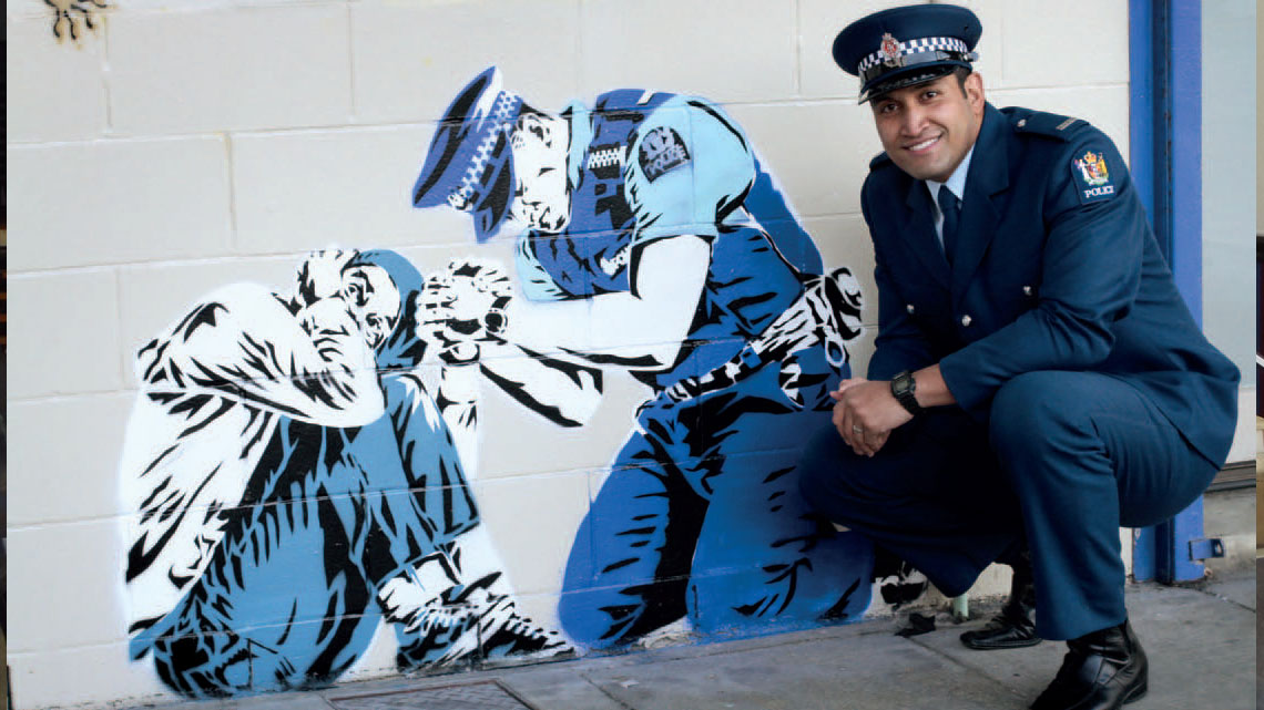 Constable Lio Kahau with graffiti art depicting him comforting a a distressed woman