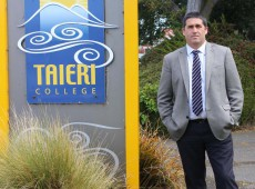Taiere College Principal Dave-Hunter stands next to the college sign