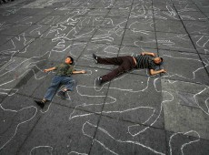 Children lie on the ground among silhouettes of people allegedly killed by soldiers during Mexico's drug war