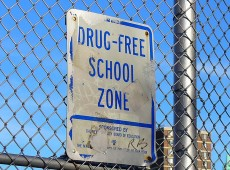 Sign behind fence: Drugs free school zone