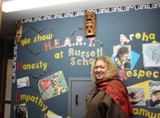 Principal Sose Annandale stands in front of a wall of positive messages at Russel School