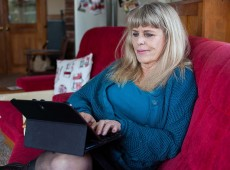 Living Sober member Lizi Reese on a couch with her tablet