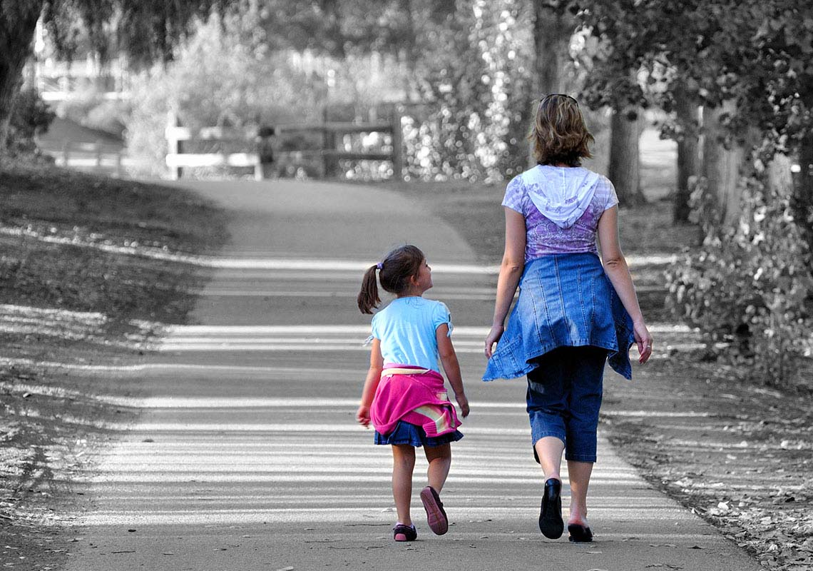 A woman and child in colour walk away along a tree-lined street in black and white