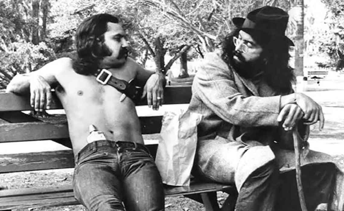 Old black and white photo from the 1970s depicts Cheech and Chong sitting on a park bench. Cheech is shirtless, and has a large joint tucked into a belt which he wears across his chest and shoulder.