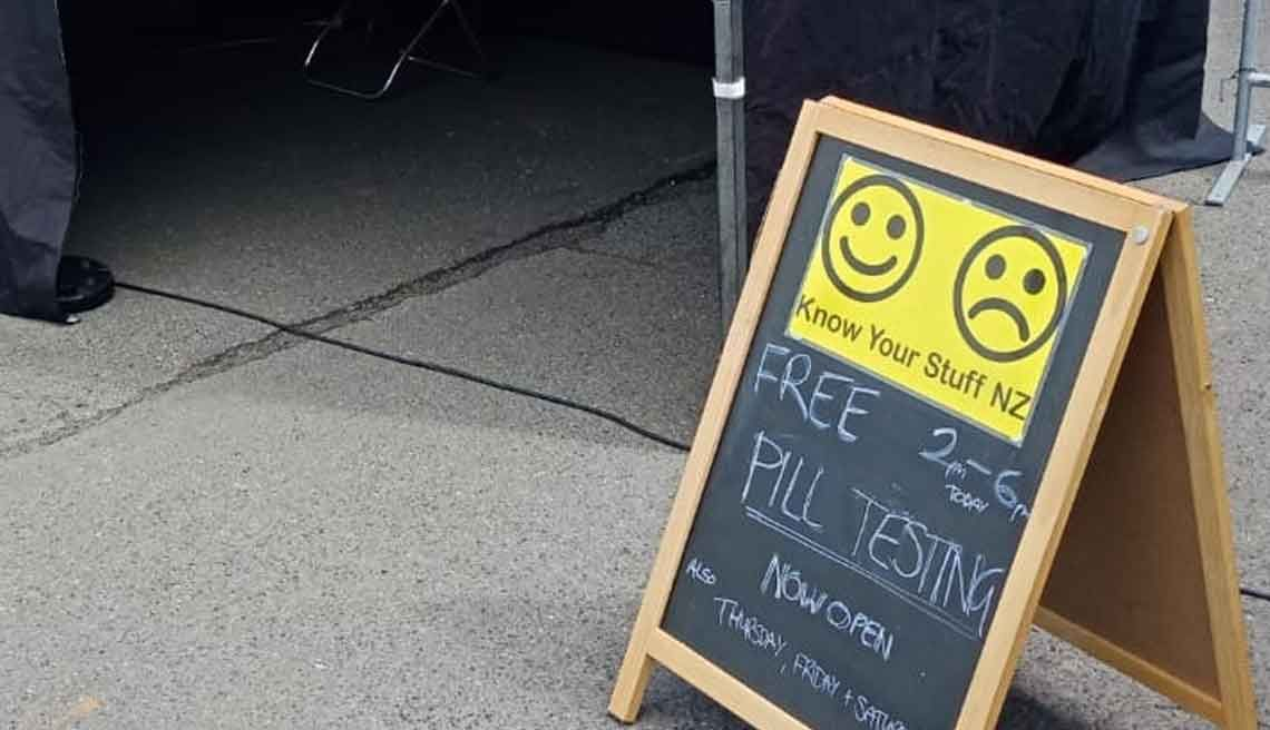 "Chalk-written sign outside tent with Know Your Stuff NZS logo, reads ""Free Pill Testing 2-6pm, Now open"""