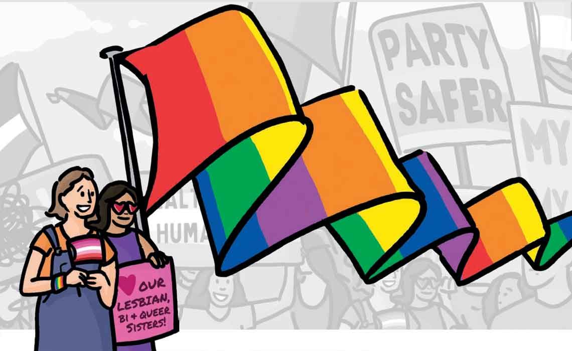 "Two women hold a giant flowing rainbow flag along with a pink placard reading ""heart our lesbian, bi and queer sisters"", against a greyscale backdrop of rally participants"