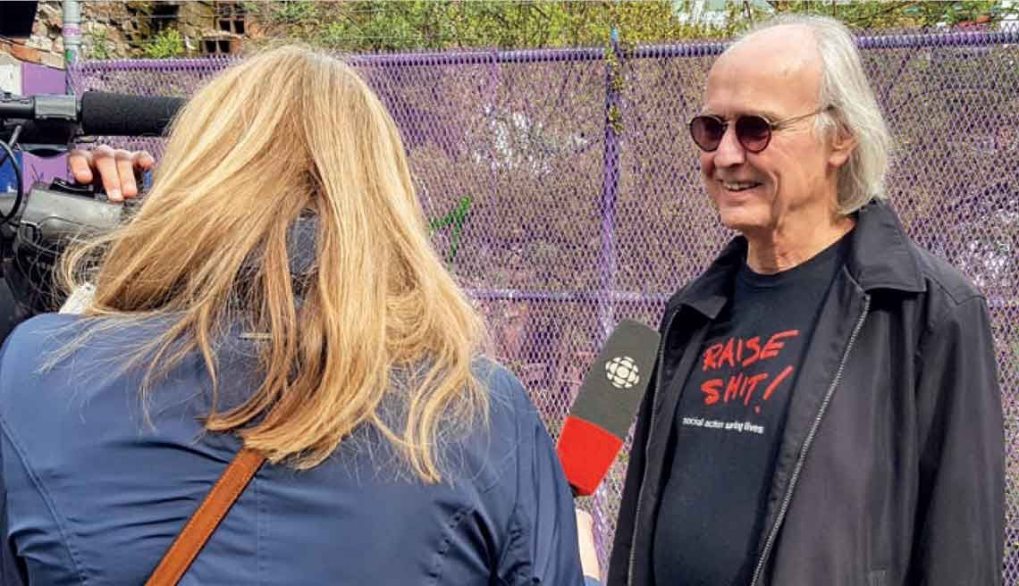 "A reporter interviews Donald MacPherson, who is wearing sunglasses and a t-shirt reading ""Raise shit!"""