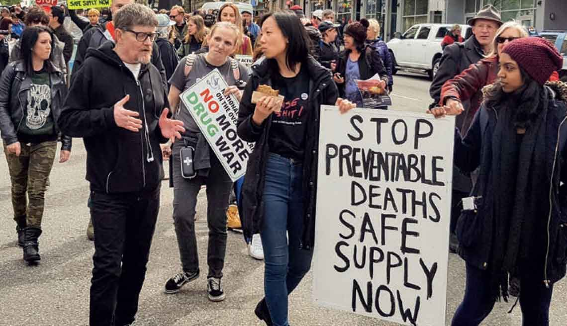 "Protesters hold a sign reading ""Stop prefentable deaths, safe supply now"" and ""No more drug war"""