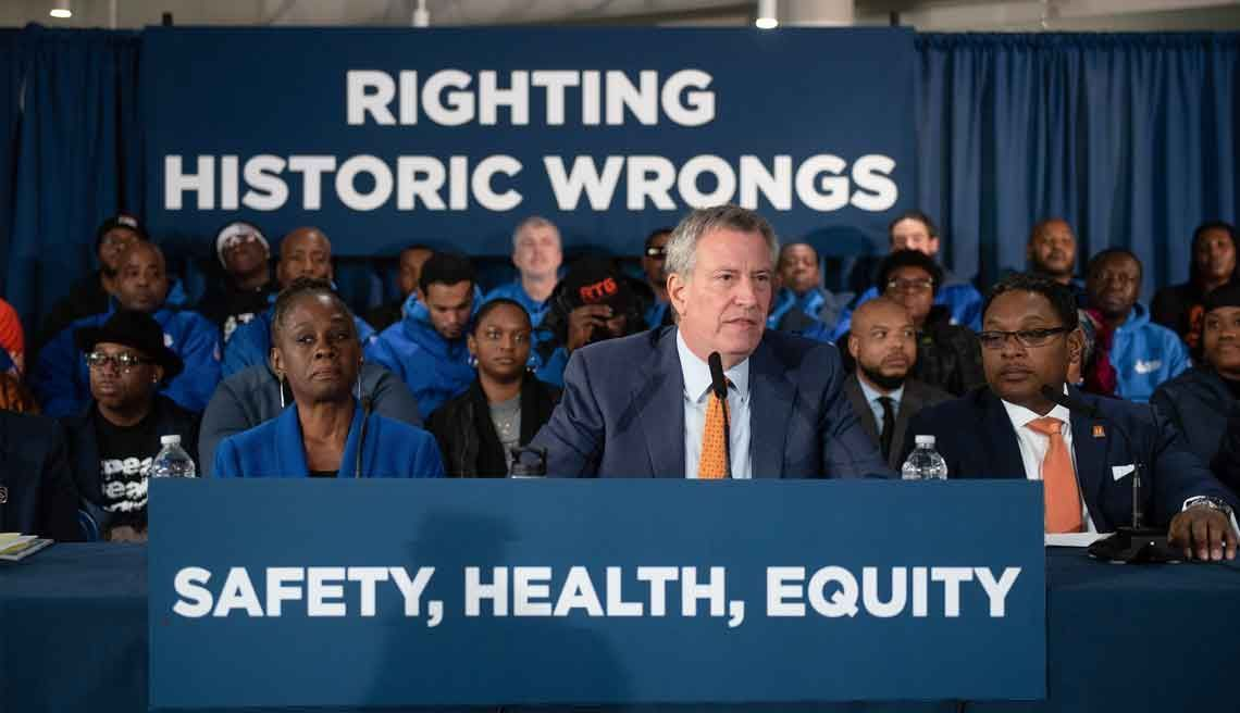 "New York Mayor Bill de Blasio speaks. Signage reads ""Righting historic wrongs"" and ""Safety, health, equity"""