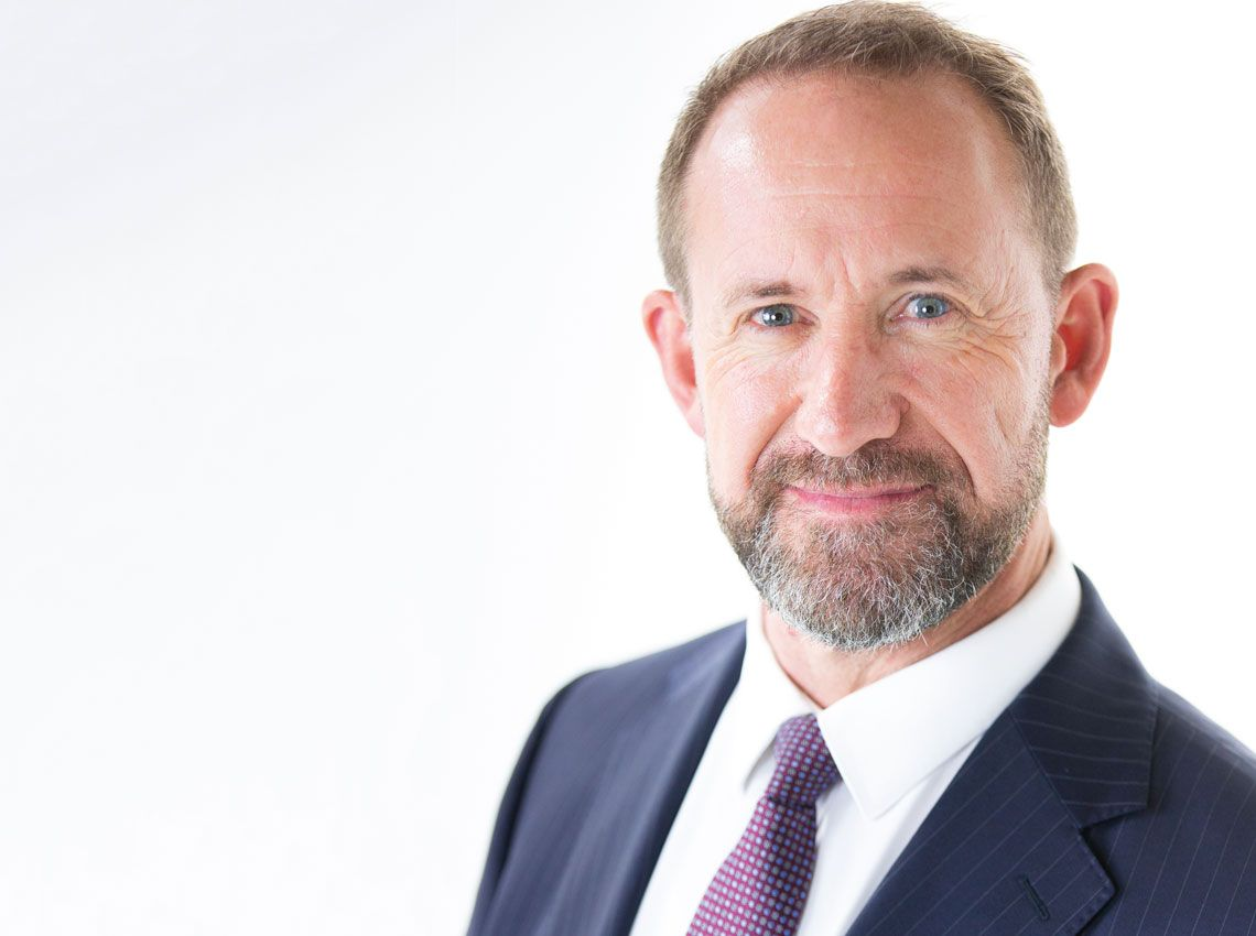 Formal photo of Andrew Little wearing a suit on a white background