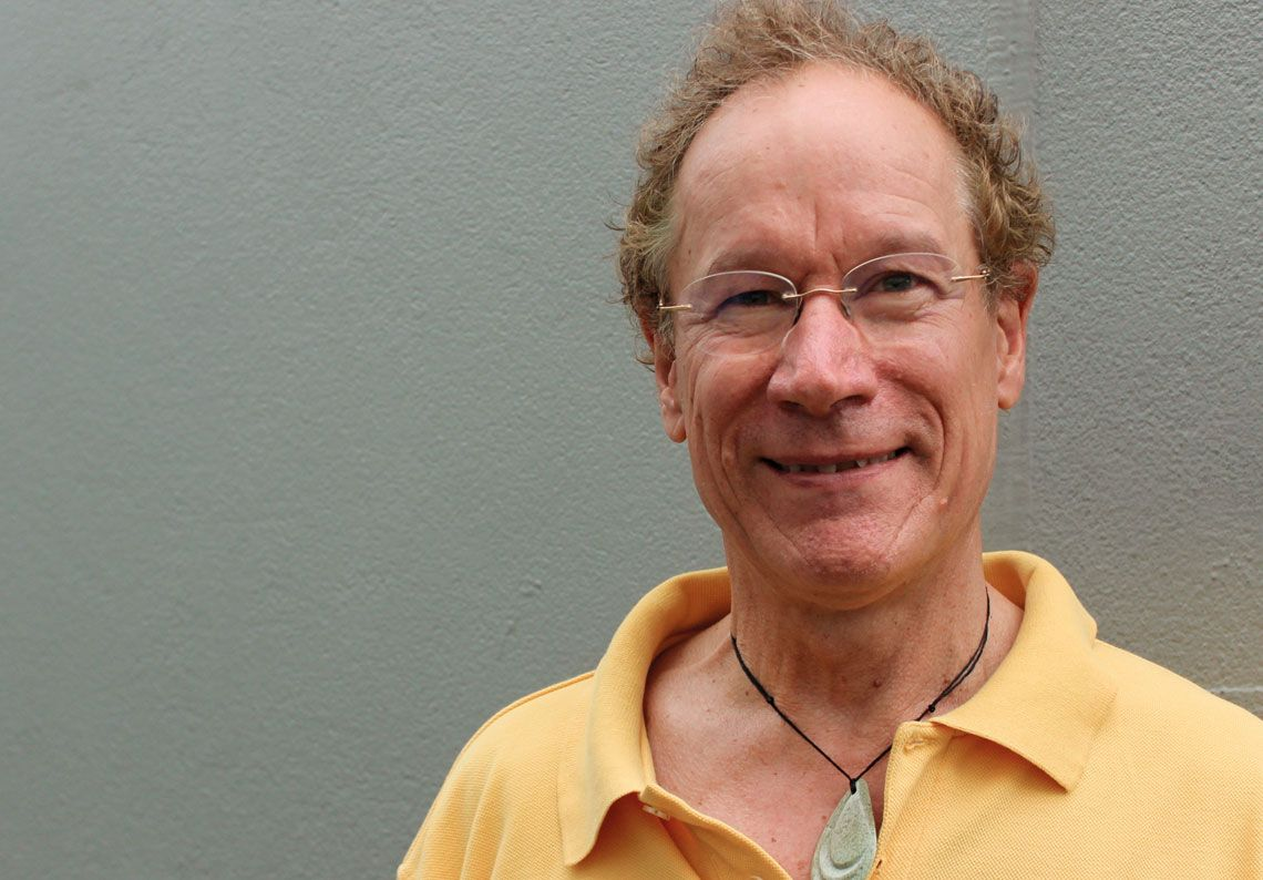 Photo portrait of Dr Graham Gulbransen wearing casual yellow shirt and pounamu, with grey background