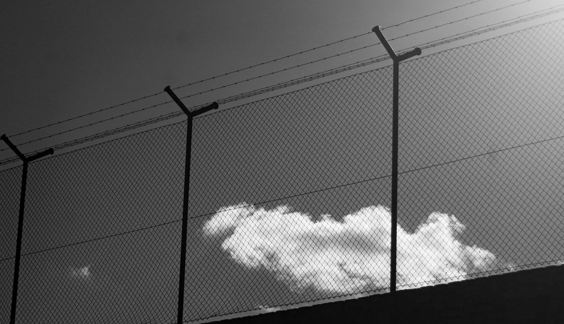 Menacing-looking black and white photo of prison surround with wire netting and barbed wire, with a cloud against a grey sky
