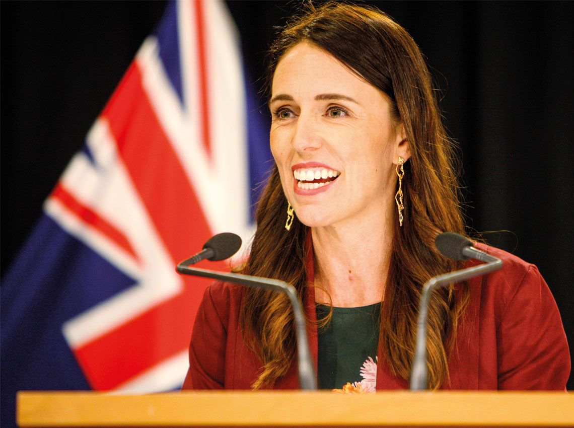 PM Jacinda Adern speaking at a podium with NZ flag behind her