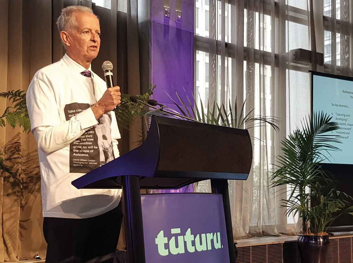 Judge Andrew Becroft holding a mic as he addresses the audience, with Tūturu logo showing on the podium