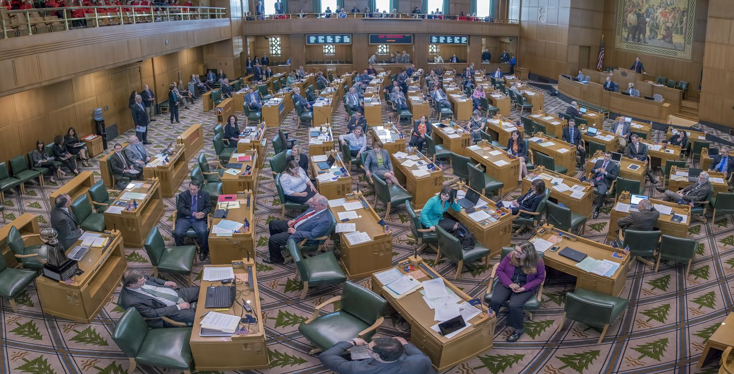 Oregon's state legislature with politicians talking at their desks